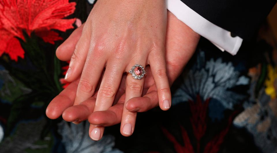 Princess Eugenie wears a ring containing a padparadscha sapphire surrounded by diamonds as she poses with Jack Brooksbank in the Picture Gallery at Buckingham Palace in London after they announced their engagement. Photo: Jonathan Brady/PA Wire