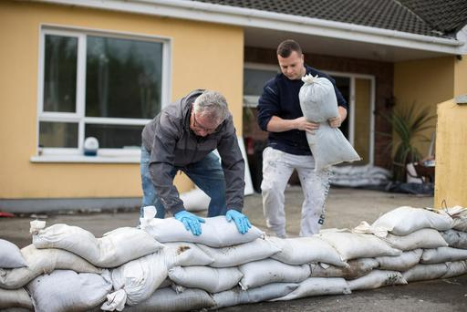 Cecil Hope gets help laying down sandbags in Mountmellick, Co Laois