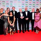 Sir David Attenborough (centre) and the Blue Planet II team in the press room with the Impact award at the National Television Awards 2018 held at the O2 Arena, London. Ian West/PA Wire