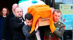 The remains of Lt Gen Gerry McMahon are carried by son Felim (centre left), grandson Ruairí (front left) and Capt Thomas Caufield (right) in Newbridge, Co Kildare. Photo: Frank McGrath