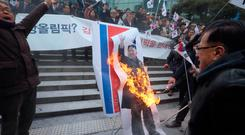 South Korean protesters burn a portrait of North Korean leader Kim Jong-un during a rally against a visit of North Korean Hyon Song Wol, head of a North Korean art troupe. Photo: AP