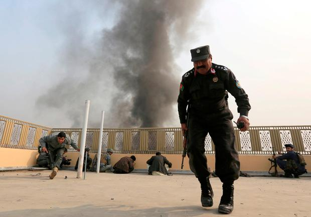 Afghan police officers take position during gun fire after the blast in Jalalabad, Afghanistan. Photos: Reuters
