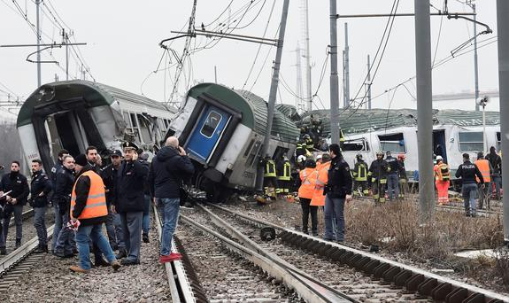Rescue workers and police officers stand near derailed trains in Pioltello, on the outskirts of Milan, Italy, January 25, 2018. REUTERS/Stringer