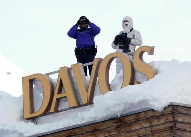 Swiss police officers observe the surrounding area from atop the roof of the Davos Congress Hotel during the World Economic Forum (WEF) annual meeting in Davos, Switzerland. Photo: Reuters