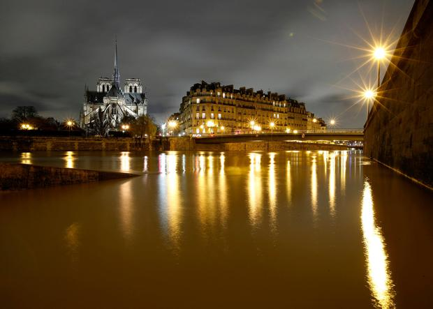 A general view shows the Notre Dame Cathedral at night, on the flooded banks of the River Seine in Paris, France, after days of almost non-stop rain caused flooding in the country, January 25, 2018. REUTERS/Christian Hartmann