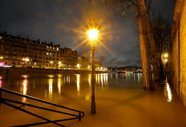 A street lamp is seen on the flooded banks of the River Seine in Paris, France, after days of almost non-stop rain caused flooding in the country, January 25, 2018. REUTERS/Christian Hartmann