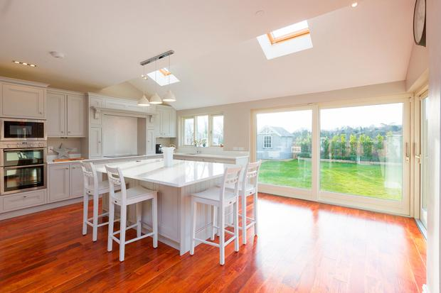 The kitchen with white granite countertops and doors to the garden