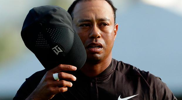 Tiger Woods takes off his cap after finishing on the South Course at Torrey Pines Golf Course