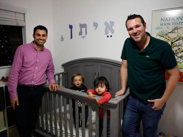 Elad Dvash-Banks, left, and his partner, Andrew, with their twin sons, Ethan, centre right, and Aiden