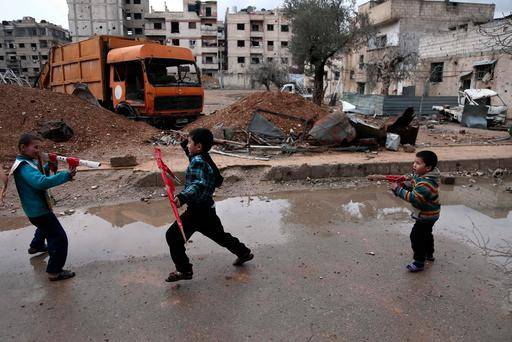 Syrian children play with cardboard guns in the rebel-held town of Harasta, in the Eastern Ghouta region on the outskirts of Damascus on January 25, 2018. / AFP PHOTO / ABDULMONAM EASSAABDULMONAM EASSA/AFP/Getty Images