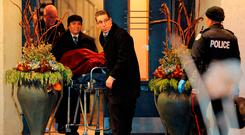 One of two bodies is removed from the home of billionaire founder of Canadian pharmaceutical firm Apotex. Photo: Reuters