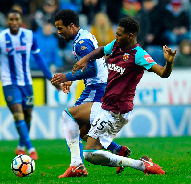 Wigan's Nathan Byrne is tackled by West Ham's Reece Oxford. Photo: Anthony Devlin/PA