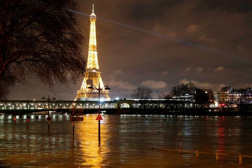 A flooded street lamp and signboards are pictured next to the river Seine in Parison the river Seine in Paris, Saturday, Jan. 27, 2018. Floodwaters were nearing their peak in Paris on Saturday, with the rain-swollen Seine River engulfing scenic quays and threatening wine cellars and museum basements. The Eiffel tower is seen background. (AP Photo/Christophe Ena)