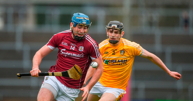 Conor Cooney of Galway tries to escape the clutches of Antrim's David Kearney. Photo by Daire Brennan/Sportsfile