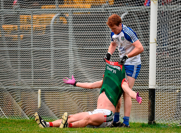 Monaghan's Kieran Duffy attemps to help Diarmuid O'Connor off the ground in Clones. Photo by Seb Daly/Sportsfile