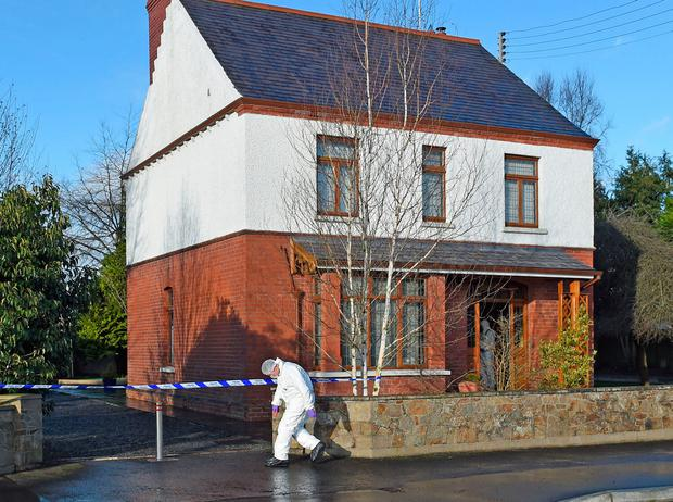 A police technical officer examines the scene in Aughnacloy, Co Tyrone