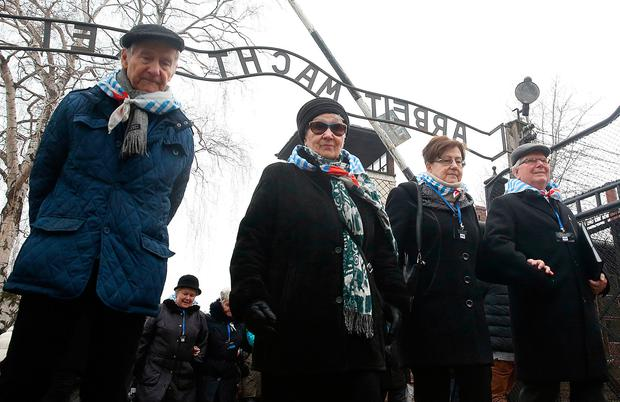 Survivors and guests walk past the 'Arbeit Macht Frei' gate at the former Nazi German concentration camp on International Holocaust Remembrance Day in Oswiecim, Poland Photo: AP Photo/Czarek Sokolowski