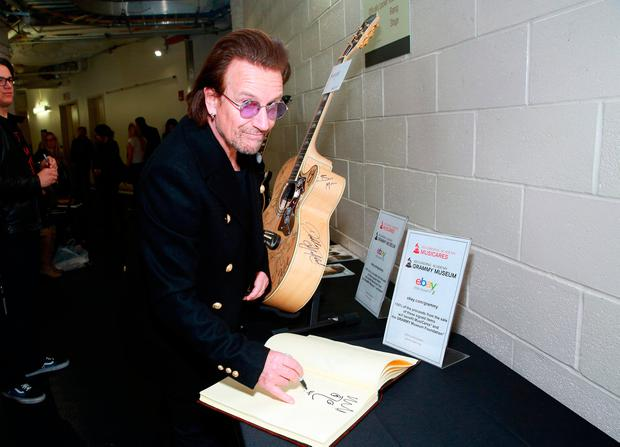 Bono pens his autograph in the Grammy Charities book in New York Photo: Robin Marchant/Getty Images for NARAS
