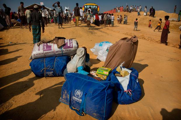 In this Sunday, Jan. 21, 2018, photo, a Rohingya refugee elderly woman guards her family belongings as others went to get relief material on reaching Balukhali refugee camp 50 kilometres (31 miles) from, Cox's Bazar, Bangladesh. (AP Photo/Manish Swarup)