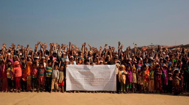 Rohingya refugee children raise their hands and shout that they won't go back to Myanmar during a demonstration at Kutupalong near Cox's Bazar, Bangladesh, Monday, Jan. 22, 2018. (AP Photo/Manish Swarup)