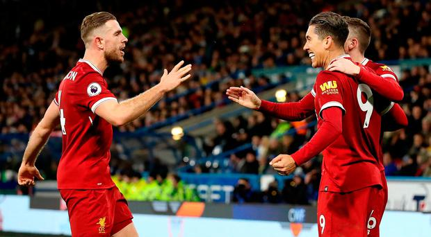 Liverpool's Roberto Firmino (right) celebrates scoring his side's second goal of the game with team-mates including Jordan Henderson (left) during the Premier League match at the John Smith's Stadium, Huddersfield. Martin Rickett/PA Wire.