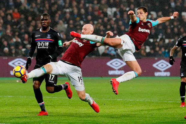 West Ham United's Javier Hernandez and James Collins stretch to reach the ball. Photo: Reuters