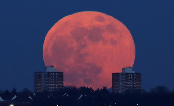 A full moon rises behind blocks of flats in north London, Britain, January 31, 2018. REUTERS/Eddie Keogh