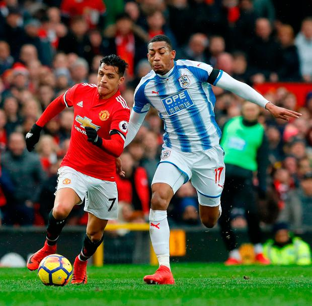 Manchester United's Alexis Sanchez (left) and Huddersfield Town's Rajiv van La Parra battle for the ball. Photo: Martin Rickett/PA