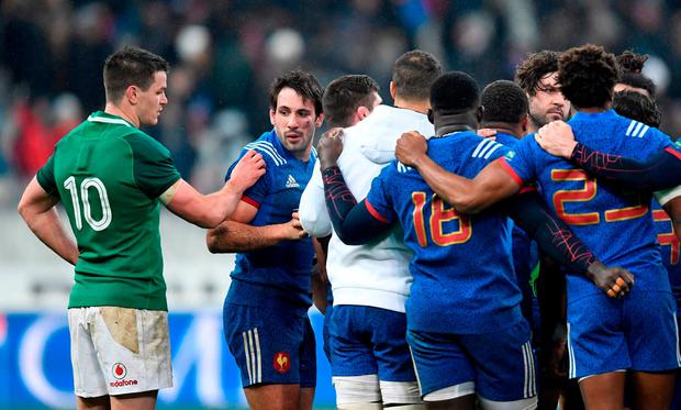 France's players react next to Ireland's fly-half Jonathan Sexton after losing the Six Nations rugby union match between France and Ireland at the Stade de France