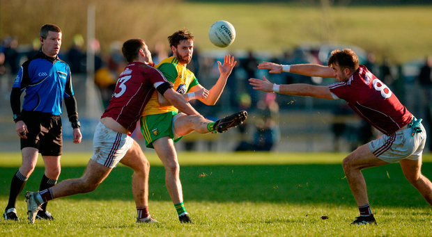 Donegal's Odhran Mac Niallais gets the ball away under pressure from Galway duo Patrick Sweeney and Paul Conroy during their defeat in O'Donnell Park. Photo by Oliver McVeigh/Sportsfile