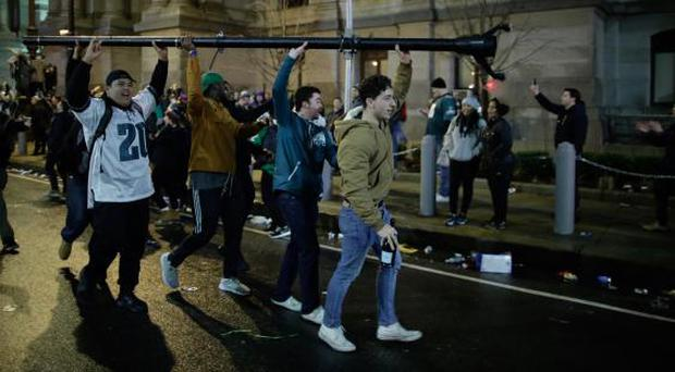 Eagles fans on the march with a lamp post (Getty)