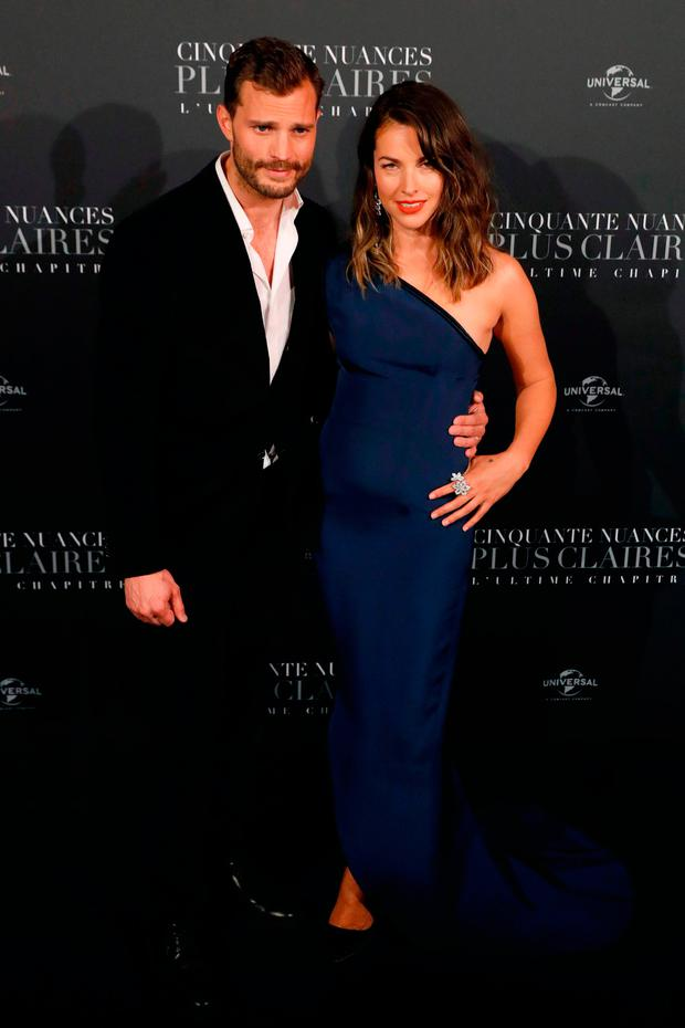 Actor Jamie Dornan (L) poses with his wife Amelia Warner as they arrive to attend 'Fifty Shades Freed - 50 Nuances Plus Claires' Premiere at Salle Pleyel in Paris on February 6, 2018. / AFP PHOTO / PATRICK KOVARIKPATRICK KOVARIK/AFP/Getty Images
