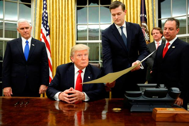 White House Staff Secretary Rob Porter (2nd R) gives US President Donald Trump, flanked by Vice President Mike Pence and Chief of Staff Reince Priebus the document to confirm Secretary of Defense James Mattis, Trump's first signing in the Oval Office in Washington, U.S., January 20, 2017. REUTERS/Jonathan Ernst/Files