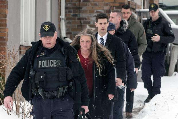Forensic anthropologist professor Kathy Gruspier, second from left, walks with police officers at a property where alleged serial killer Bruce McArthur worked, Thursday, Feb. 8, 2018 in Toronto. Toronto police say they've recovered the remains of at least 6 people from a property connected to alleged serial killer Bruce McArthur. (Chris Young/The Canadian Press via AP)