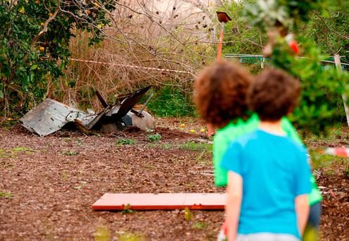 Under fire: Children in Alonei Abba, east of Haifa, northern Israel, cautiously look at the remains of a missile that crashed in their back garden. Picture: Jack Guez/Getty