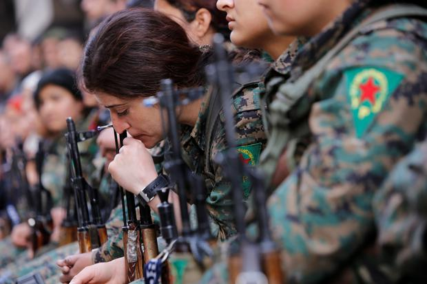 A Kurdish female fighter of the Women's Protection Unit (YPJ) gestures as she sits in the Sheikh Maksoud neighbourhood of Aleppo, Syria February 7, 2018. Picture taken February 7, 2018. REUTERS/Omar Sanadiki