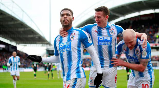 Huddersfield Town's Steve Mounie celebrates scoring their third goal with Jonathan Hogg and Aaron Mooy