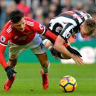 Alexis Sanchez collides with Matt Ritchie as they battle for possession. Photo: Getty Images