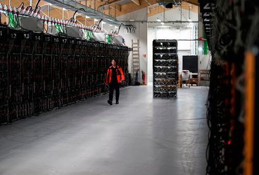 A worker walks along a row of computer rigs that run around the clock 'mining' bitcoin inside the Genesis Mining cryptocurrency mine in Keflavik Iceland