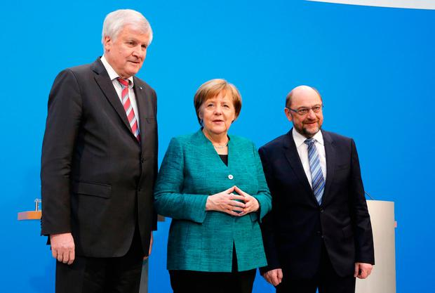 German Chancellor Angela Merkel, CDU, is flanked by Martin Schulz, chairman of the Social Democratic Party and Bavarian Governor Horst Seehofer, chairman of the Christian Social Union, during a press statement after Merkel's conservatives and Germany's main center-left party reached a deal to form a new coalition government. (AP Photo/Ferdinand Ostrop)