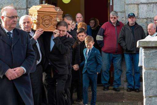 Leo (right) and Kory (centre) Miller, sons of former Celtic and Manchester United footballer Liam Miller, follow their father's coffin at his funeral at St John the Baptist Church in Ovens, Co Cork. Photo: PA