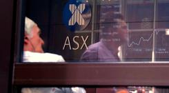 A pedestrian is reflected in a window where an investor sits looking at a board displaying stock prices at the Australian Securities Exchange (ASX) in Sydney