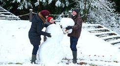 Frankie McCafferty, Ophelia Byrne and Theo McCafferty (11), from Belfast, beside their snowman at Farnham Estate in Cavan. Photo: Damien Eagers