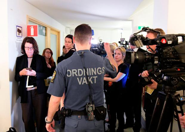 A security guard and journalists stand outside the court room, where the trial against the terror suspect, Uzbekistan citizen Rakhmat Akilov, who is suspect for terror attack in the central parts of Stockholm in April last year, started in Stockholm District Court, Stockholm, Sweden February 13, 2018. TT News Agency/Janerik Henriksson via REUTERS