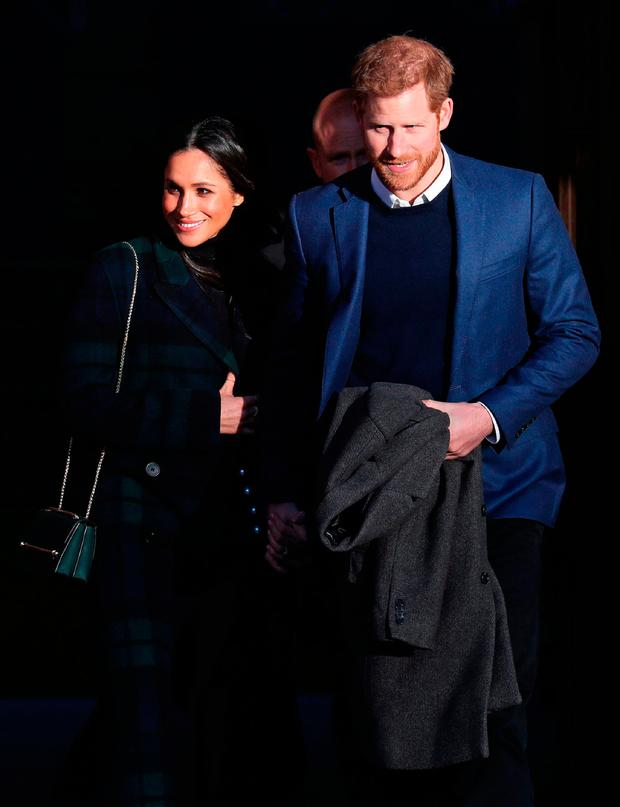Britain's Prince Harry (R) and his fiancée US actress Meghan Markle leave a reception for young people in the Palace of Holyroodhouse in Edinburgh, during their visit to Scotland on February 13, 2018
