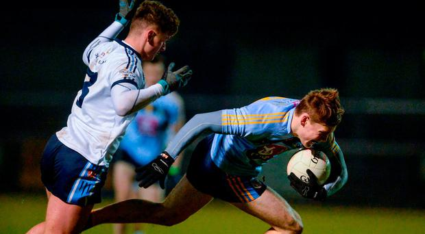 UCD's Con O'Callaghan stumbles under pressure from Michael McKernan of Ulster University during last night's extended Sigerson Cup semi-final. Photo: OLIVER MCVEIGH/SPORTSFILE