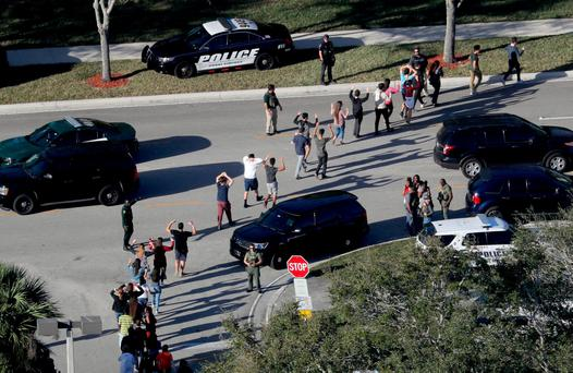 Students hold their hands in the air as they are evacuated by police from Marjorie Stoneman Douglas High School in Parkland, Fla., on Wednesday, Feb. 14, 2018, after a shooter opened fire on the campus. (Mike Stocker/South Florida Sun-Sentinel via AP)