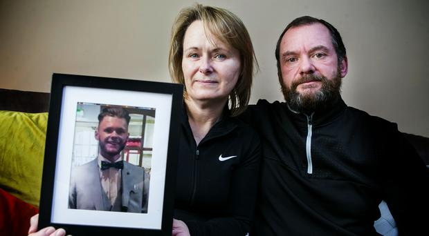Catherine and Mark Grimes holding a photograph of their late son Callum (Cal ) Grimes