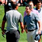 Tiger Woods and Rory McIlroy shake hands after finishing their round during the first round of the Genesis Open at Riviera Country Club