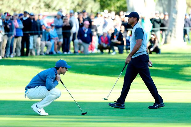 Tiger Woods walks by as Rory McIlroy lines up a putt on the 14th green at Riviera Country Club. Photo: Getty Images